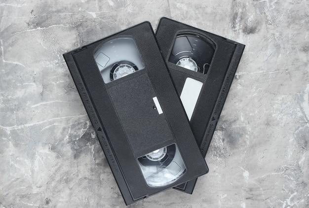 Retro vhs video cassettes from the 80s on a gray concrete surface. the oldest media