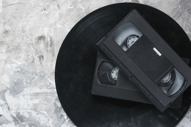 Retro vhs videocassettes from the 80s and vinyl records on a gray concrete background. the oldest media. top view