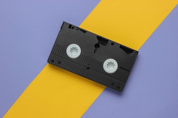 黄紫色の背景にレトロなビデオカセット