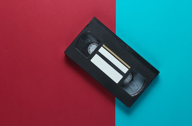 Retro video cassette on a red-blue table. top view