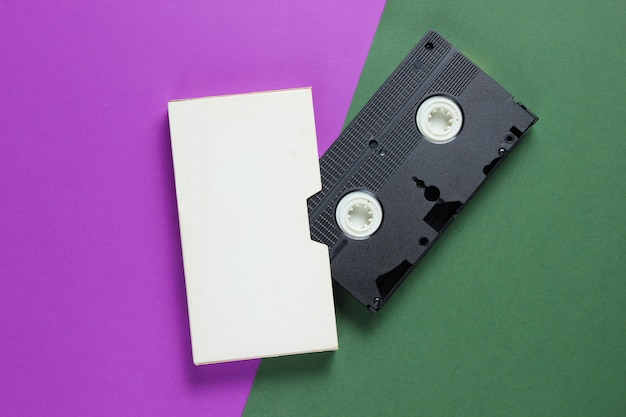 Retro video cassette with cover on color paper surface.
