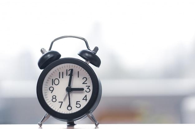 ウィンドウ - 時間とスタートアップの概念の横にある木のテーブルにレトロなビンテージの目覚まし時計