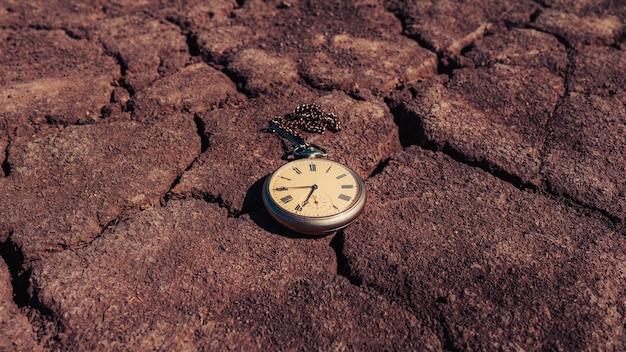 레트로 빈티지 골동품 시계 회중 시계, 마른 땅의 배경에 거짓말. 과거 또는 미래 시제의 개념.