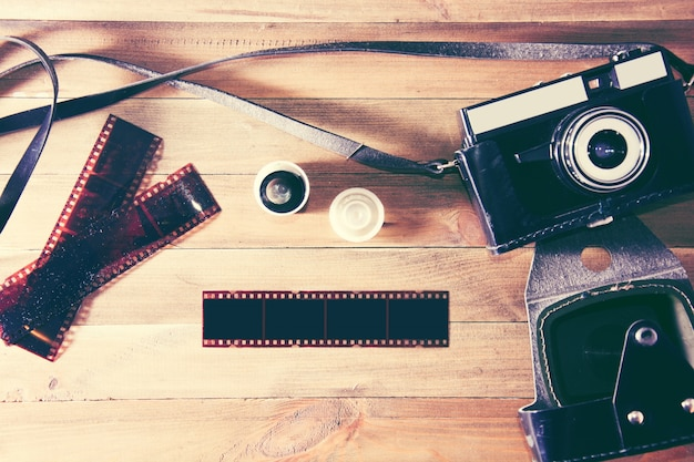 Retro vintage camera and photographic film on wooden background