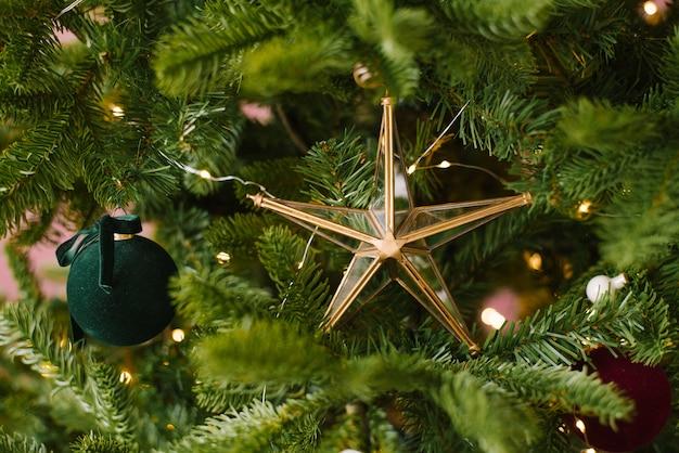 ライトと木の上のレトロなヴィンテージのクリスマスのおもちゃのガラスの星