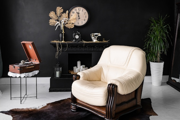 レトロなヴィンテージインテリア。ダークブラック色のレトロなリビングルームのインテリア。レトロな革張りの椅子と暖炉