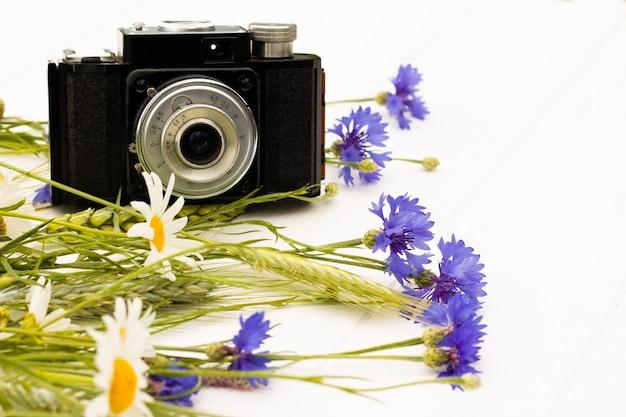 흰색 나무 배경에 수레국화와 데이지가 있는 레트로 빈티지 오래 된 카메라. 복사 공간