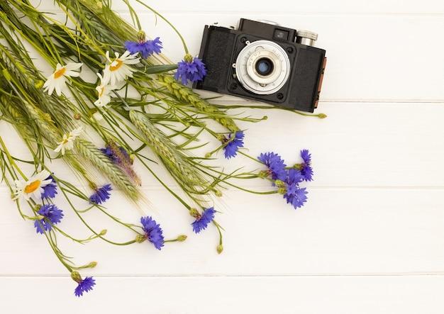 흰색 나무 배경에 수레국화와 데이지가 있는 레트로 빈티지 오래 된 카메라. 평면도. 공간을 복사합니다.