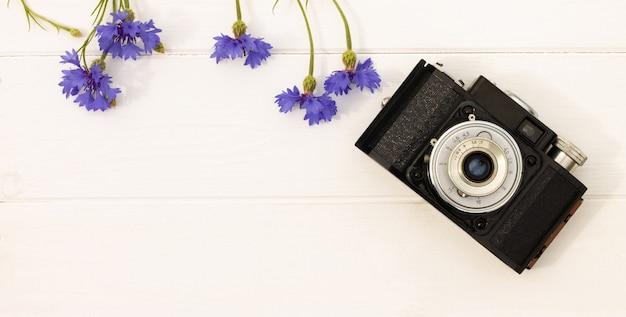 흰색 나무 바탕에 수레 국화와 레트로 빈티지 오래 된 카메라. 평면도. 공간을 복사합니다. 배너