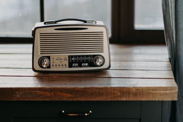 窓の近くの木製のテーブルの表面にレトロなビンテージラジオ。 80年代に戻る。音楽の郷愁と古い技術の概念。アンティークレコーダー