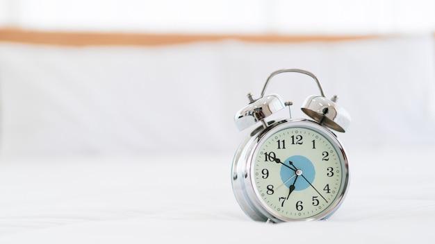 Retro vintage style analog alarm clock on the white bed