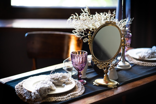 レトロなヴィンテージテーブル。テーブル、アンティークミラー、プレート、ヴィンテージマグカップのアレンジメント。テーブルの上の古代の鏡