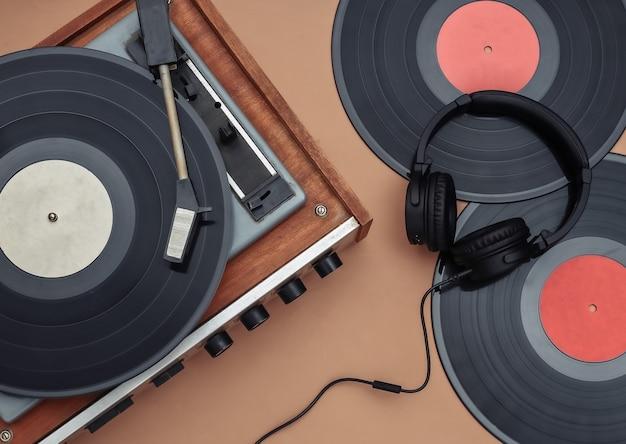 茶色の背景にレトロなビニールプレーヤーとステレオヘッドフォン。上面図。フラットレイ