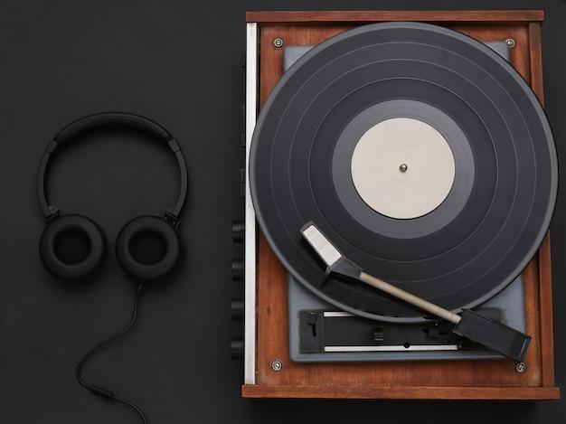 黒の背景にレトロなビニールプレーヤーとステレオヘッドフォン。上面図。フラットレイ