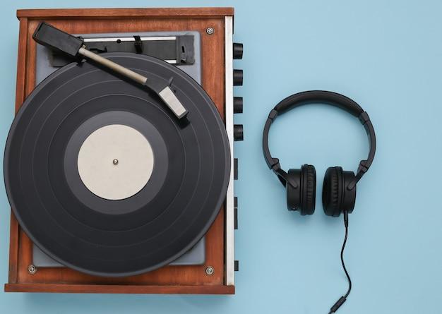 青い背景のレトロなビニールプレーヤーとステレオヘッドフォン。上面図。フラットレイ