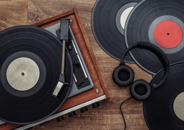 木製の背景にレトロなビニールプレーヤーとステレオヘッドフォン。上面図。フラットレイ