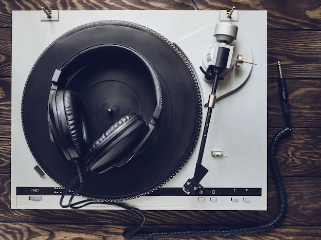 Retro vinyl player and old headphones on a wooden table