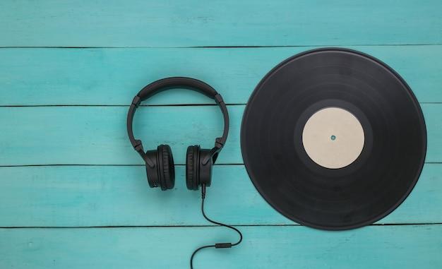 青い木製の背景にレトロなビニールレコードとステレオヘッドフォン。上面図。フラットレイ