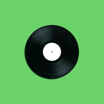 Retro vinyl record disk with blank white label on green background