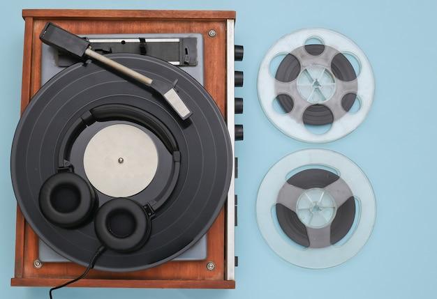 青い背景のレトロなビニールレコードプレーヤーと磁気オーディオリール。上面図