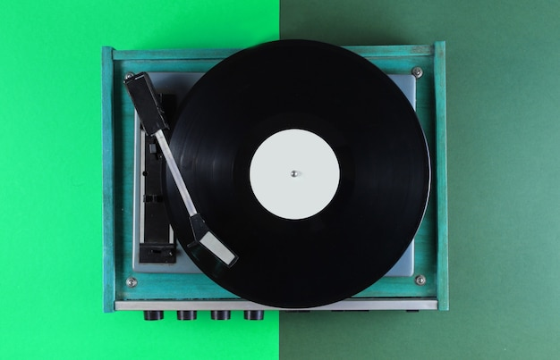 Retro vinyl record player on green
