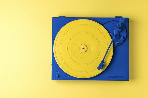 노란색 바탕에 세련 된 색 구성표에 레트로 비닐 레코드 플레이어. 복고풍 음악 장비.