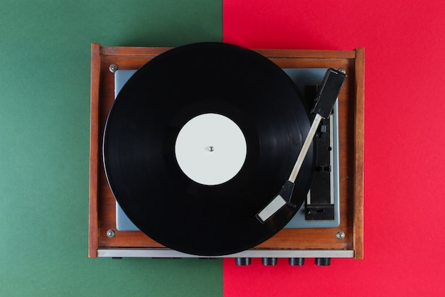 Retro vinyl record player on red green surface
