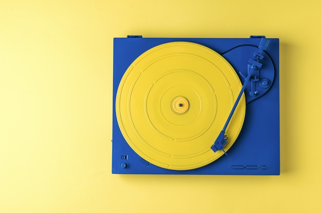 Retro vinyl record player in a stylish color scheme on a yellow background. retro music equipment.