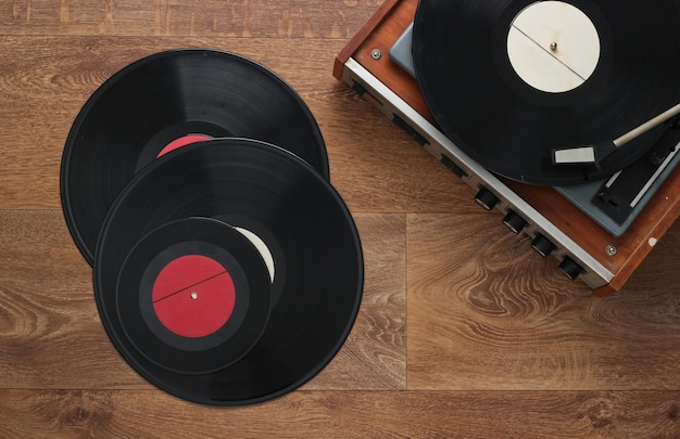 Ретро виниловый проигрыватель с пластинками на полу. 80-е гг. вид сверху