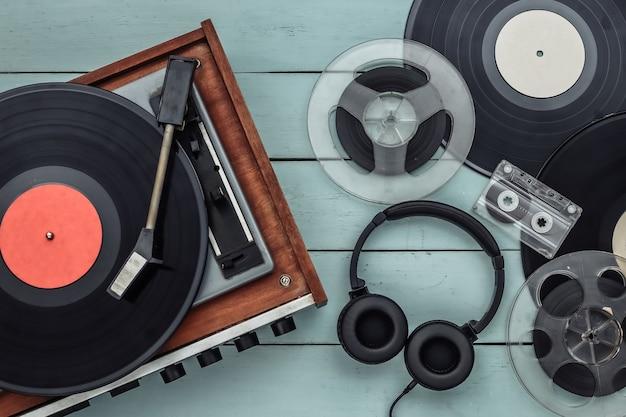 青い木製の背景にレコード、オーディオ磁気リール、オーディオカセット、ステレオヘッドフォンを備えたレトロなビニールレコードプレーヤー。上面図。フラットレイ