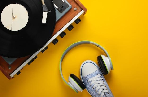 黄色の表面にステレオヘッドフォンとスニーカーを備えたレトロなビニールレコードプレーヤー