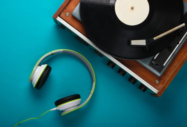 Retro vinyl record player with stereo headphones on blue surface