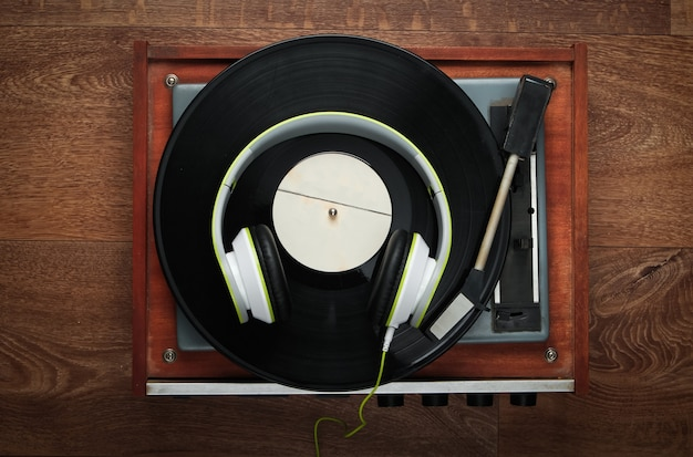 木の床にステレオヘッドフォンを備えたレトロなビニールレコードプレーヤー