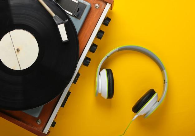黄色の表面にステレオヘッドフォンを備えたレトロなビニールレコードプレーヤー