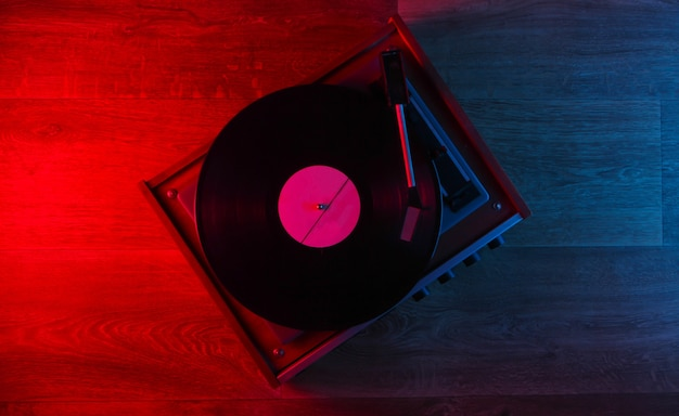 Retro vinyl record player on a wooden floor with blue-red neon light