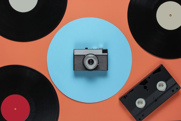 Retro vinyl record video cassette, film camera on a coral color background with a blue circle. top view