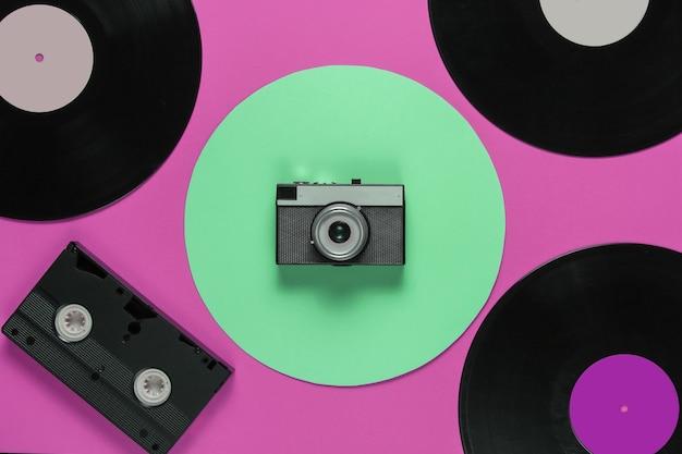 복고풍 비닐 레코드 비디오 카세트, 녹색 원이 있는 분홍색 배경의 필름 카메라. 평면도
