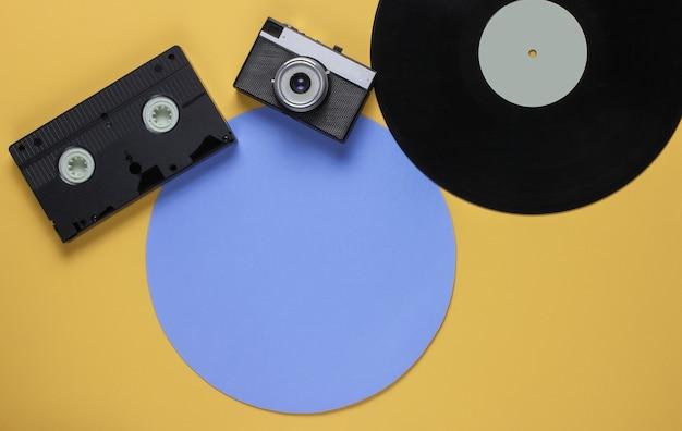 파란색 원이 있는 노란색 배경의 복고풍 비닐 레코드, 비디오 카세트, 필름 카메라. 평면도