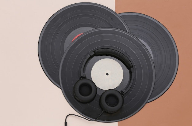 茶色のベージュの背景にレトロなビニールレコードとステレオヘッドフォン。上面図。フラットレイ