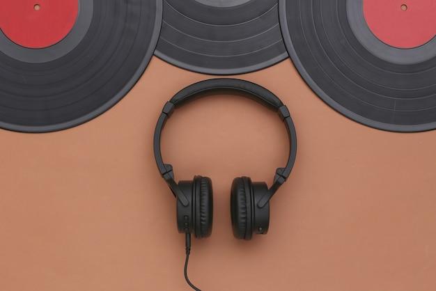 茶色の背景にレトロなビニールレコードとステレオヘッドフォン。上面図。フラットレイ
