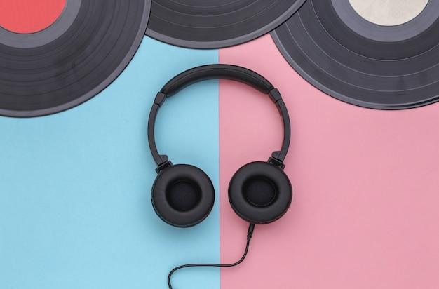 ピンクブルーのパステルカラーの背景にレトロなビニールレコードとステレオヘッドフォン。上面図。フラットレイ
