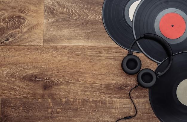 木製の背景にレトロなビニールレコードとステレオヘッドフォン。スペースをコピーします。上面図。フラットレイ