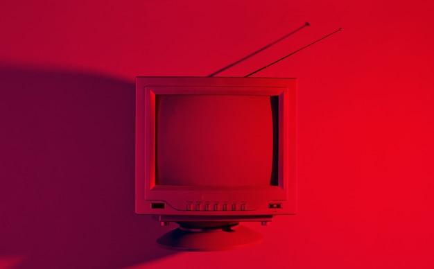 레트로 웨이브, 80 년대. 붉은 네온 빛으로 안테나와 오래 된 tv. 탑 뷰, 미니멀리즘
