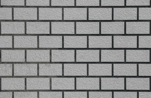 Retro weathered old gray brick stack fence wall surface texture background.
