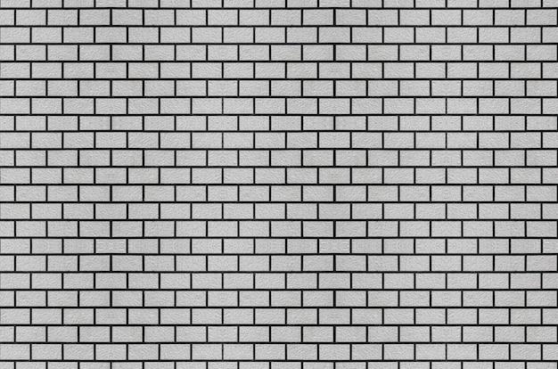Retro weathered old gray brick stack masonry wall surface background.