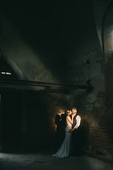 Retro wedding couple inside the old church on the ray of sun.