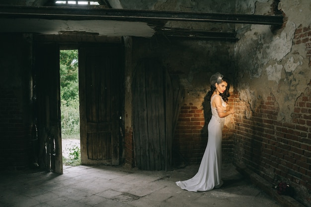 Retro wedding couple inside the old church on the ray of sun