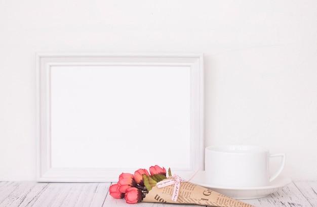 Ретро белая рамка старинный деревянный стол и кофейная чашка цветок