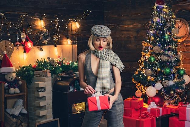 크리스마스 트리 배경 위에 샴페인 레트로 여자입니다. 크리스마스 선물 상자 뷰티 패션 소녀입니다.