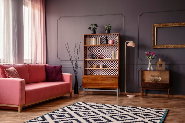 Retro wooden cupboard with books and decorations standing in dark room interior with pink sofa, carpet and flowers in glass vase